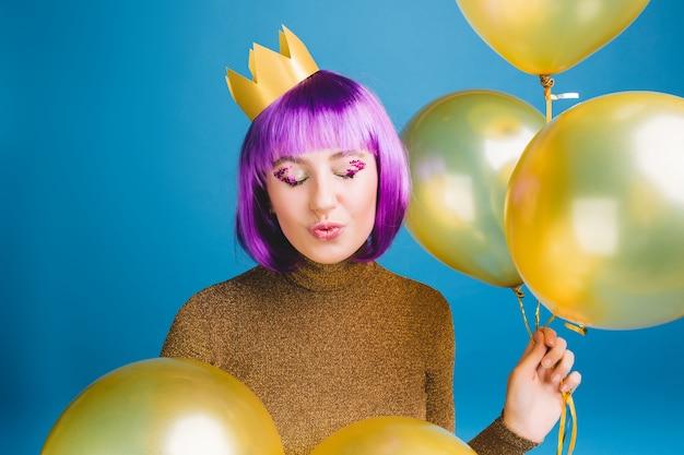 Porträt freudige junge frau mit geschnittenem lila haar, das spaß hat. goldene luftballons, kuss mit geschlossenen augen, krone auf dem kopf, luxuskleid, tolle party, feier. Kostenlose Fotos