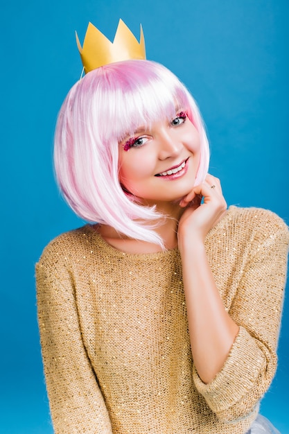 Porträt fröhliche junge frau mit geschnittenem rosa haar, im goldenen pullover und in der krone auf dem kopf lächelnd. positivität ausdrücken, wahre emotionen, großartige neujahrsparty feiern. Kostenlose Fotos