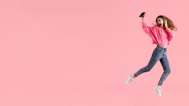Porträt glückliche frau, die springt und musik hört Kostenlose Fotos