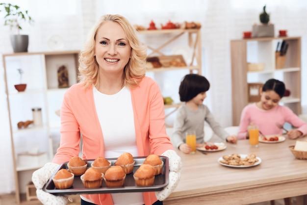 Porträt-glückliche großmutter-halteplatte mit muffins Premium Fotos