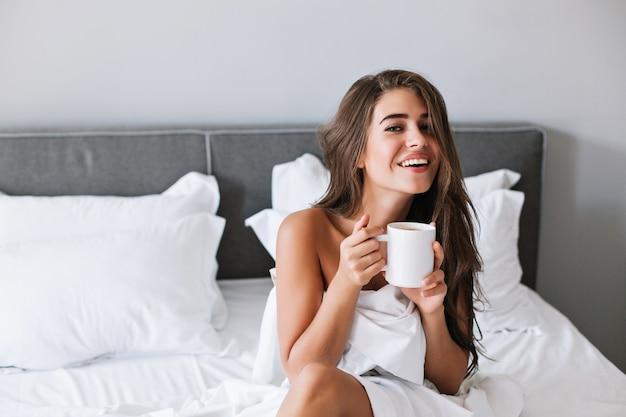 Porträt hübsches mädchen mit frechen schultern, die kaffee auf bett am morgen in der wohnung trinken. Kostenlose Fotos