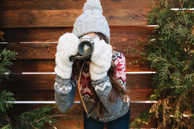Porträt hübsches mädchen mit langen haaren in strickmütze und handschuhen machen ein foto vor der kamera auf holz. Kostenlose Fotos
