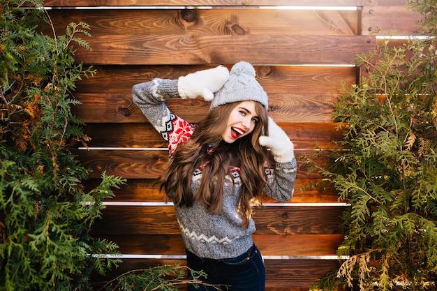 Porträt hübsches mädchen mit langen haaren in strickmütze und winterpullover auf holz. sie hält die hände in handschuhen und lacht. Kostenlose Fotos