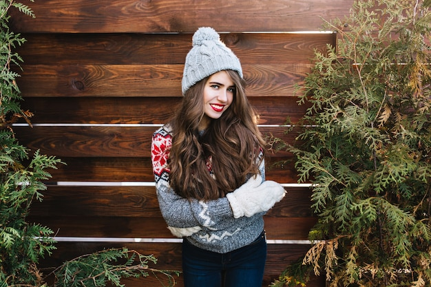 Porträt hübsches mädchen mit langen haaren in winterkleidung und warmen handschuhen auf holz. sie lächelt . Kostenlose Fotos