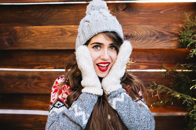 Porträt hübsches mädchen mit langen haaren und roten lippen in strickmütze auf holz. sie berührt das gesicht in warmen handschuhen und lächelt. Kostenlose Fotos