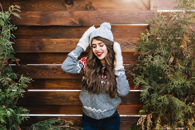 Porträt hübsches mädchen mit langen haaren und roten lippen in strickmütze und warmen handschuhen auf holz. sie lächelt und hält die augen geschlossen. Kostenlose Fotos