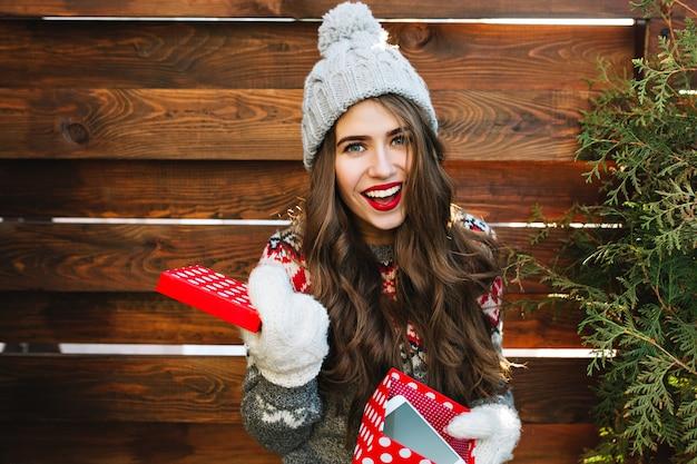 Porträt hübsches mädchen mit langen haaren und roten lippen mit weihnachtsbox auf holz. sie trägt eine strickmütze, handschuhe und lächelt. Kostenlose Fotos