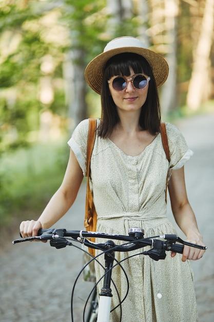 Porträt im freien des attraktiven jungen brunette in einem hut auf einem fahrrad. Kostenlose Fotos