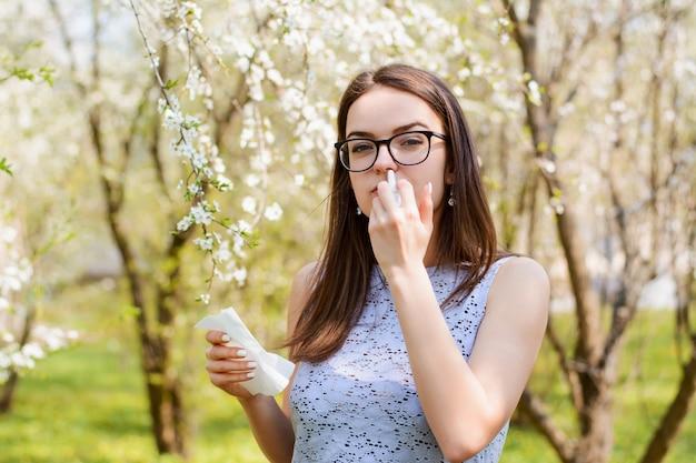 Porträt im freien des jungen mädchens mit allergie auf saisonpollen, benutzt taschentuch und nasenspray, wirft über blühendem baum auf, hat rhinitis und niesen. menschen und krankheitskonzept Premium Fotos