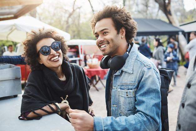 Porträt im freien eines glücklichen afroamerikanischen paares mit afro-frisuren, das sich auf tisch während des lebensmittelfestivals stützt, zeit zusammen verbringt und auf ihre bestellung wartet. Kostenlose Fotos