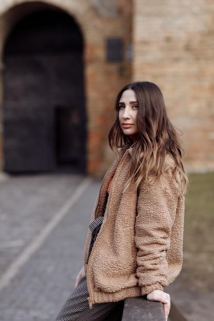 Porträt im modestil. schönes stilvolles mädchen mit langen haaren geht in die stadt. porträt des attraktiven mädchens auf der straße. frühling oder herbst tag. selektiver fokus. Premium Fotos