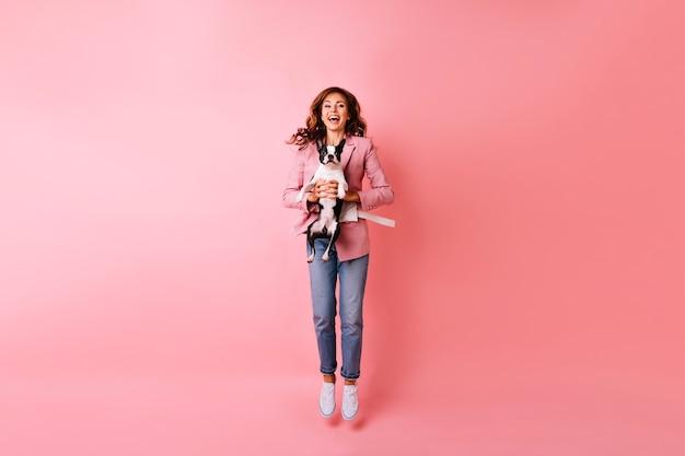 Porträt in voller länge der ekstatischen jungen frau, die mit französischer bulldogge springt. innenporträt des emotionalen rothaarigen mädchens, das mit ihrem haustier kühlt. Kostenlose Fotos