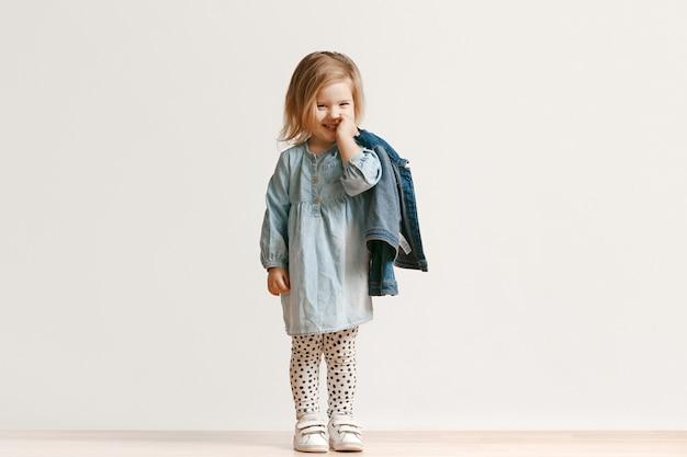 Porträt in voller länge des niedlichen kleinen kindermädchens in der stilvollen jeanskleidung und lächelnd, auf weiß stehend. kindermode-konzept Kostenlose Fotos