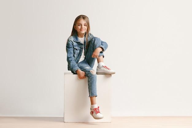 Porträt in voller länge des niedlichen kleinen teen in stilvollen jeans-kleidern, die kamera betrachten und lächeln Kostenlose Fotos