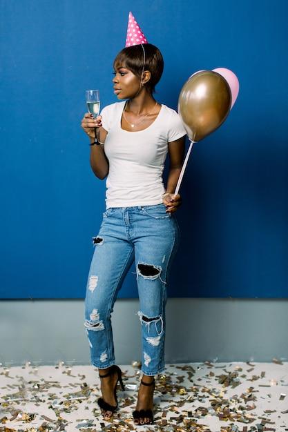 Porträt in voller länge einer fröhlichen jungen afrikanischen frau, die bündel luftballons und champagner lokalisiert über blauem raum hält. geburtstagsfeier, feierkonzept. Premium Fotos