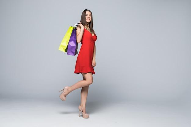 Porträt in voller länge einer glücklichen aufgeregten frau im roten kleid stehend und hält bunte einkaufstaschen lokalisiert auf einer weißen wand Kostenlose Fotos