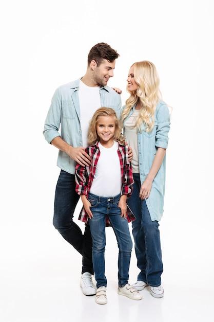 Porträt in voller länge einer jungen schönen familie, die zusammen steht Kostenlose Fotos