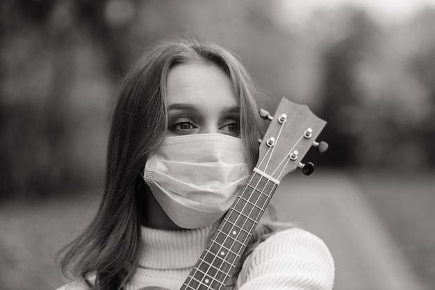 Porträt junge frau in der schutzmaske, die ukulelegitarre im herbstpark, gesundes reisekonzept des lebensstils spielt Premium Fotos