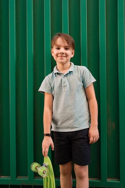Porträt junger kühler lächelnder junge im blauen polo, der mit penny board aufwirft Kostenlose Fotos