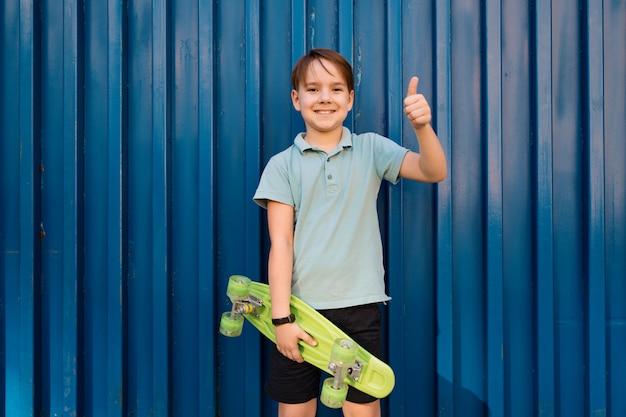 Porträt junger kühler lächelnder junge im blauen polo, der mit penny board in den händen aufwirft Kostenlose Fotos