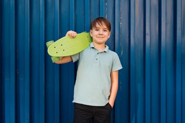 Porträt junger kühler lächelnder junge im blauen polo, der mit schlittschuh auf der schulter und hand in einer tasche aufwirft Kostenlose Fotos