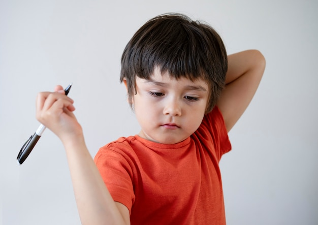 Porträt-kinderjunge, der einen stift schaut unten mit gelangweiltem gesicht hält. Premium Fotos