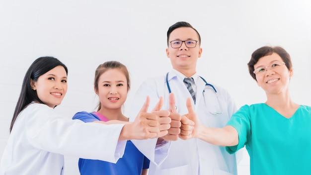Porträt lächelnden asiatischen medizinischen männlichen doktors, der sich handdaumen mit teampersonal im krankenhaus steht und zeigt. Premium Fotos