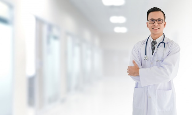 Porträt lächelnden asiatischen medizinischen männlichen doktors, der vor unscharfem innenkrankenhaus steht Premium Fotos