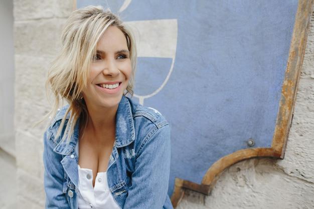 Porträt lächelnden blondine in einer denimjacke Kostenlose Fotos