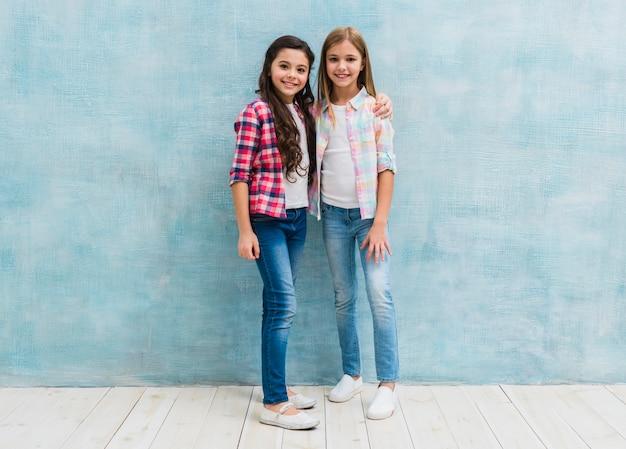 Porträt lächelnder freundin zwei, die vor blauer wand aufwirft Kostenlose Fotos