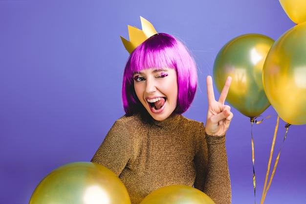 Porträt lustige junge frau mit lila haarschnitt spaß haben. goldene luftballons umgeben, zeigen zunge, drücken positive gesichtsgefühle aus, krone auf kopf, geburtstagsfeier. Kostenlose Fotos