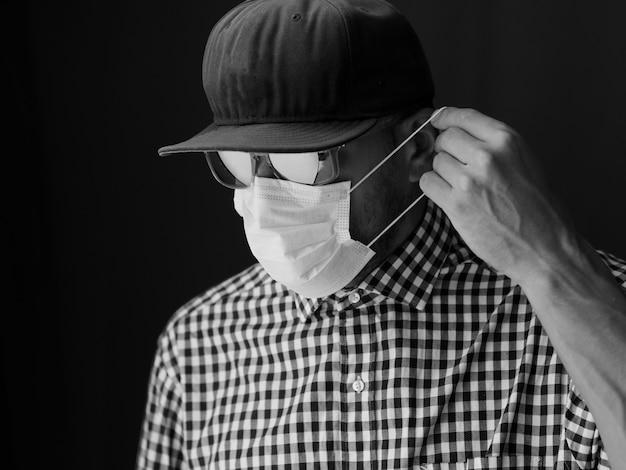 Porträt männchen mit mütze und sonnenbrille, medizinische gesichtsmaske aufsetzen. schwarzweißbild. Premium Fotos