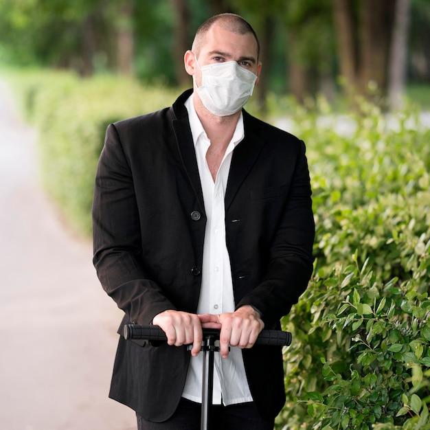 Porträt mit medizinischer maske, die roller reitet Kostenlose Fotos
