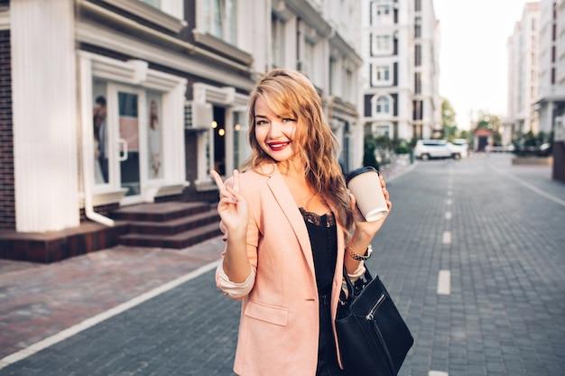 Porträt modische blonde frau mit langen haaren, die in korallenjacke auf straße gehen. sie hält eine tasse kaffee Kostenlose Fotos