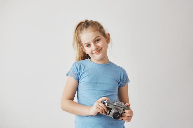 Porträt o gut aussehendes blondes kind im blauen t-shirt lächelnd, stehend mit fotokamera in den händen, die für schulalbum aufwerfen. Kostenlose Fotos