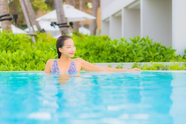 Porträt schöne junge asiatische frau entspannen freizeit um freibad mit meer ozean strand Kostenlose Fotos
