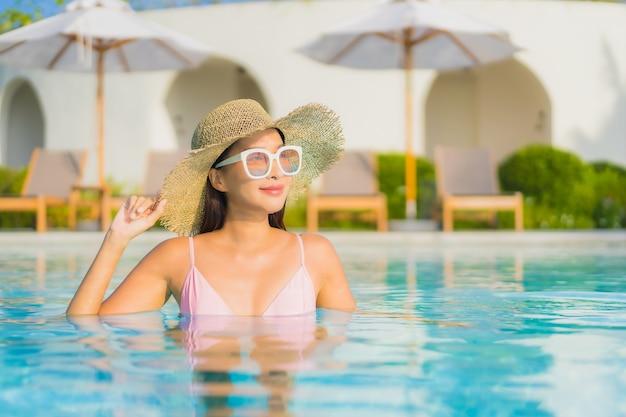 Porträt schöne junge asiatische frau entspannen freizeit um freibad mit meer Kostenlose Fotos