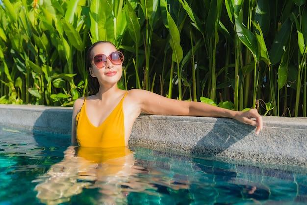 Porträt schöne junge asiatische frau entspannen glückliches lächeln um freibad im hotel resort für freizeiturlaub Kostenlose Fotos