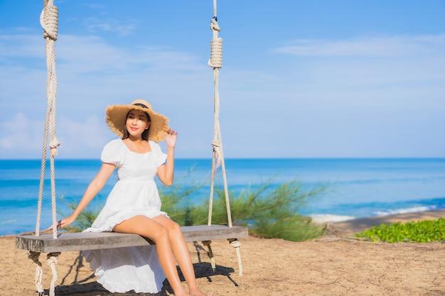 Porträt schöne junge asiatische frau entspannen lächeln auf schaukel um strand meer ozean für naturreisen im urlaub Kostenlose Fotos
