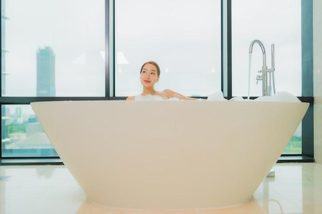 Porträt schöne junge asiatische frau entspannen lächeln freizeit in der badewanne im badezimmer interieur Kostenlose Fotos