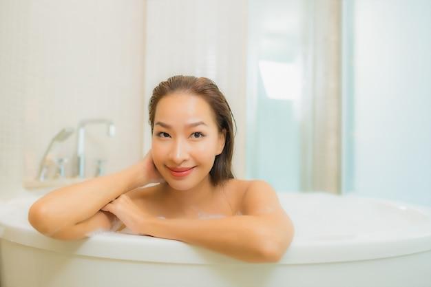 Porträt schöne junge asiatische frau entspannen lächeln in der badewanne am badezimmer interieur Kostenlose Fotos