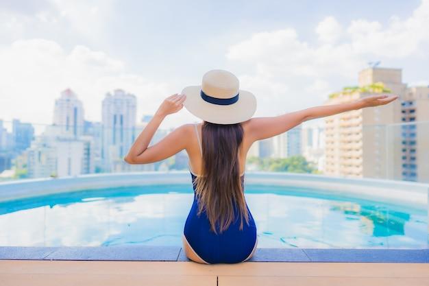 Porträt schöne junge asiatische frau entspannen lächeln um außenpool im hotel resort Kostenlose Fotos