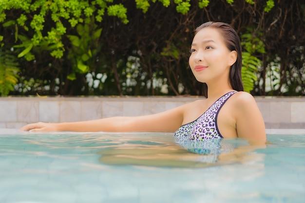 Porträt schöne junge asiatische frau entspannen lächeln um freibad für freizeit und urlaub Kostenlose Fotos