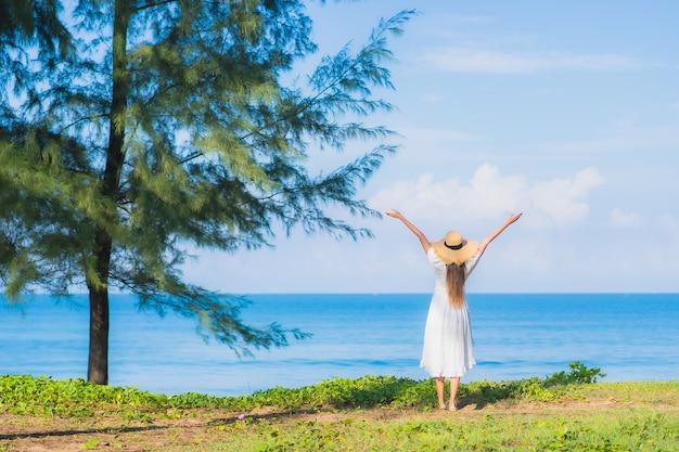 Porträt schöne junge asiatische frau entspannen lächeln um strand meer ozean mit weißer wolke des blauen himmels für reiseurlaub Kostenlose Fotos