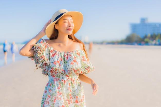Porträt schöne junge asiatische frau glückliches lächeln entspannen um tropischen strand meer ozean Kostenlose Fotos