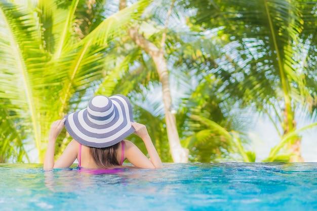 Porträt schöne junge asiatische frau lächeln entspannen um außenpool im resort hotel auf urlaub urlaub reise reise Kostenlose Fotos