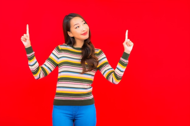 Porträt schöne junge asiatische frau lächeln mit aktion auf rote isolierte wand Kostenlose Fotos