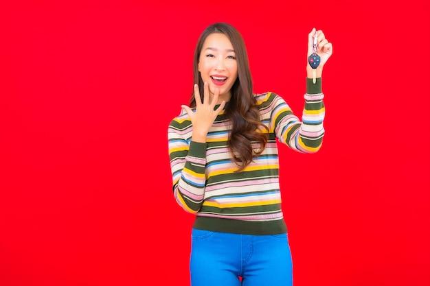 Porträt schöne junge asiatische frau mit autoschlüssel auf roter isolierter wand Kostenlose Fotos