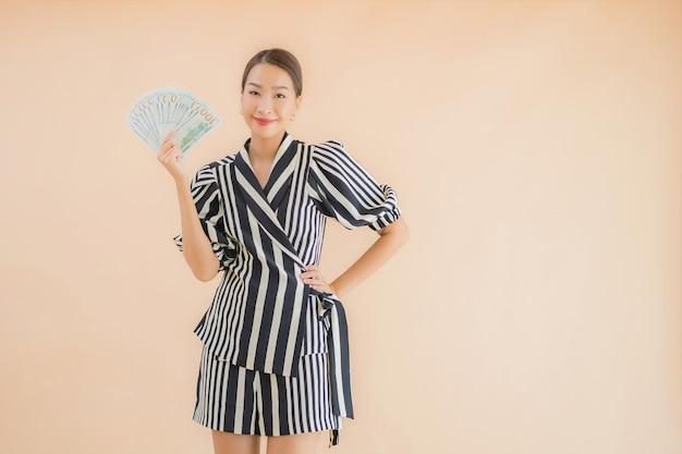 Porträt schöne junge asiatische frau mit bargeld und geld Kostenlose Fotos