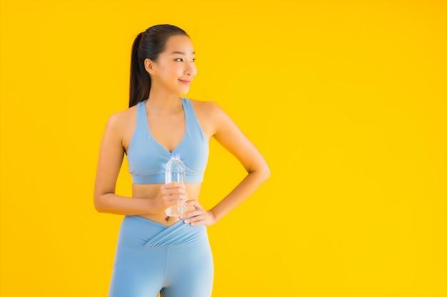 Porträt schöne junge asiatische frau mit flaschenwasser auf gelb Kostenlose Fotos